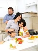 Happy family of four members in kitchen Stock Photos