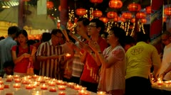 Thai Family Praying by Candlelight at a Temple During Chinese New Year Stock Footage