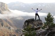 Stock Photo of man on top of mountain with open arms. conceptual design.