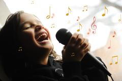 Musician kid singing with microphone Stock Photos