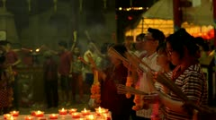 Thai People Praying by Candlelight at a Temple During Chinese New Year Stock Footage
