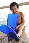 kid on pool with flippers on feet - stock photo