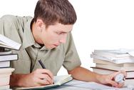 Stock Photo of young man is writting between lot of books