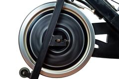 Aged spinning bike flywheel rotating. front detail. Stock Photos