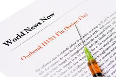 outbreak swine flu newspaper headline with syringe - stock photo