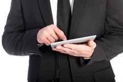 businessman scrolling on a tablet - stock photo
