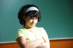 Cute girl standing in front of board in classroom Stock Photos
