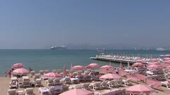 CANNES mediterranean beach with pink parasols + pan boulevard Stock Footage
