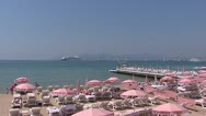 Stock Video Footage of CANNES mediterranean beach with pink parasols + pan boulevard