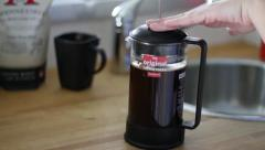 Pressing plunger down on French press coffee Stock Footage