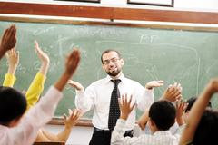 Stock Photo of good teacher in classroom in front of the board