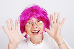 senior woman with pink hair and facial gesture - stock photo