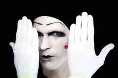 portrait of  artful peeping mime in white gloves - stock photo