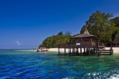 Puinen laituri ja pieni sukellus vene trooppisella saarella Kuvituskuvat