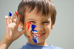 kid with color on his fingers and face smiling - stock photo