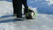 Man draw water frozen lake ice hole pour bucket winter season Stock Footage