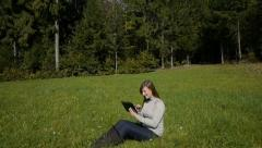 AERIAL: Young woman sitting in forest glade using a digital tablet Stock Footage