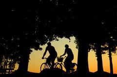 People cycling at sunset Stock Photos