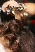 Working hairstylist curling hair in a salon Stock Photos