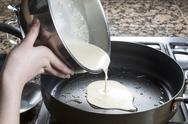 Pouring pancake mix into hot frying pan Stock Photos
