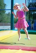 The little girl  on a trampoline in park Stock Photos