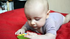 Baby plays on a red blanket Stock Footage