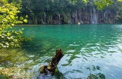 summer waterfalls and green  limpid lake - stock photo