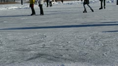 People skate slide ice outdoor frozen lake pond cold winter day Stock Footage