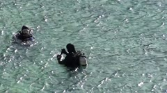 Divers put on mask and fin - stock footage