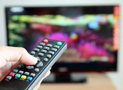 hand pointing a tv remote control towards the television - stock photo