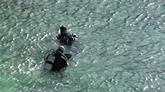 Divers putting on mask hood and fin - stock footage