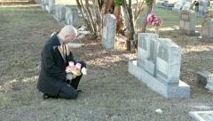 Man walks to grave & kneels medium - stock footage