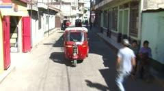 Tuk-tuks (or autorickshaws) driving in Santiago Atitlán, Guatemala. Stock Footage