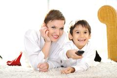 Stock Photo of mom with son lying on floor and watching tv using remote control
