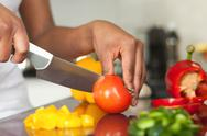 African  american womans hand slicing a tomatoe Stock Photos