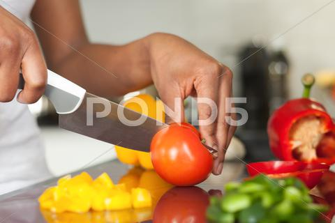 Stock photo of african  american womans hand slicing a tomatoe