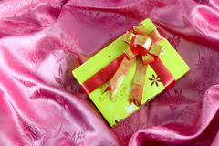 Yellow gift box with ribbon on pink satin Stock Photos