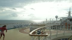 HD Stock Footage 1080p - Cruise Ship young girl fights wind on top deck Stock Footage