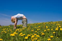 Young female excercising yoga on flowery meadow Stock Photos
