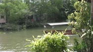 An Empty Tourist Boatsell Passes a Riverside Cabin Stock Footage