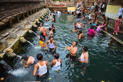 purification in sacred holy spring water, bali - stock photo