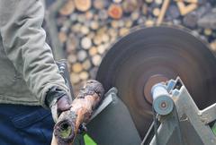 Man sawing wood on the circular saw. Stock Photos