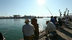 Dolly shot of the fishermen in the port of Sochi Stock Footage