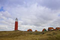 red lighthouse and houses on island texel, the netherlands - stock photo