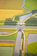 Dutch farm landscape with infrastructure road and canal Stock Photos