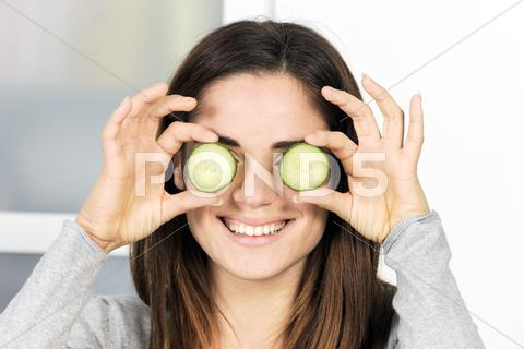 Stock photo of woman holding slice of cucumber