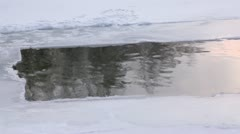 Water waves and reflection on water in ice hole at winter day Stock Footage