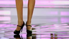 Girls in shoes on long heel stand on stage, closeup Stock Footage