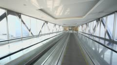Escalator ride through tunnel with glass walls at sunny day Stock Footage