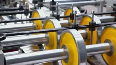 Several shafts and wheels spins in machine of printing conveyer Stock Footage
